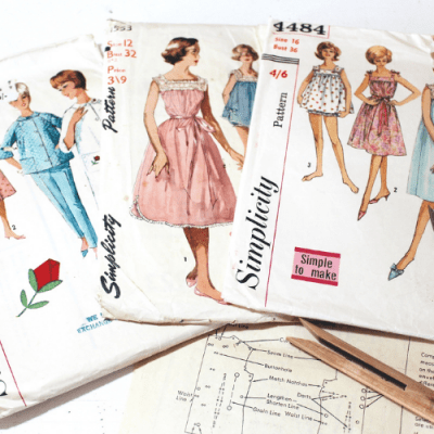vintage sewing patterns and spools laying on makylas sewing table