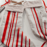 handmade christmas stockings laying on white sewing table