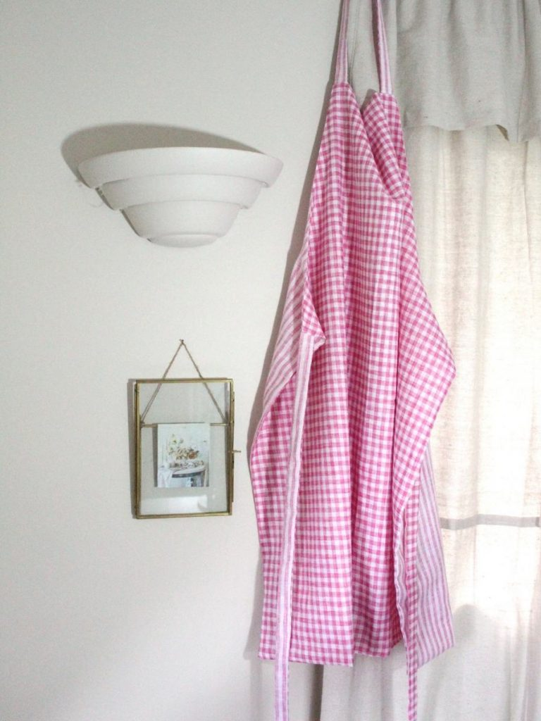 how to make an apron. pink and white gingham apron hanging on the wall next to a pretty vintage photo frame