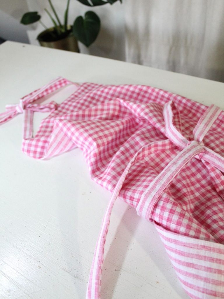 how to make an apron step by step. Apron is laying on a white table. The waist tie is tied into a pretty bow.