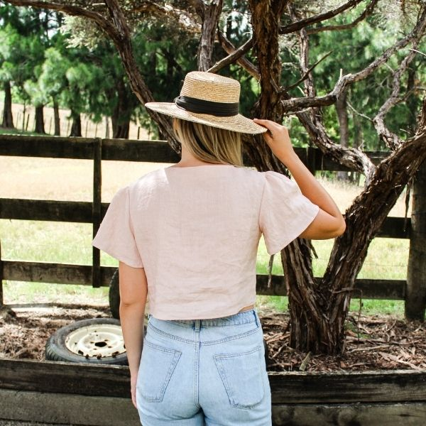 Shania wearing pink linen camille top with front ties and flute sleeves. Close up of the back of camille top. There are paddocks and fences behind her.