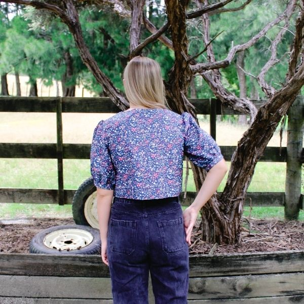 shania wearing blue and floral camille top with puff sleeve. Standing on a farm with trees and paddocks behind. Close up of back of camille top