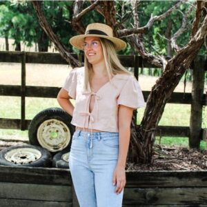 Shania wearing pink linen camille top with front ties and flute sleeves. She is smiling and wearing a straw hat. There are paddocks and fences behind her.