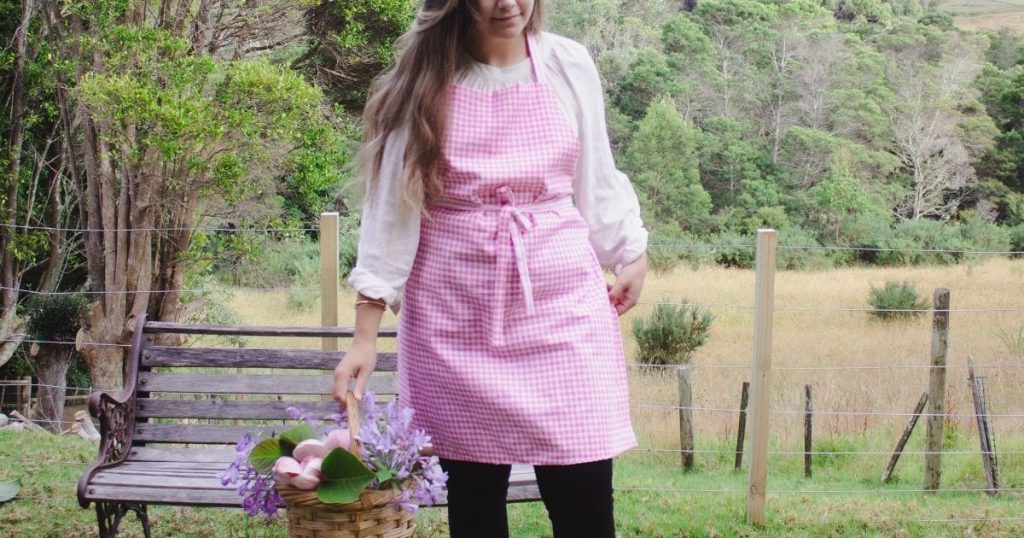 makyla wearing apron while holding basket of flowers in the garden.