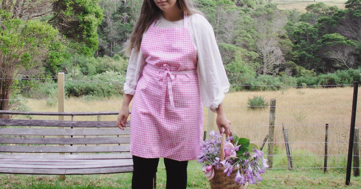 makyla wearing reversible apron with basket of flowers in hand