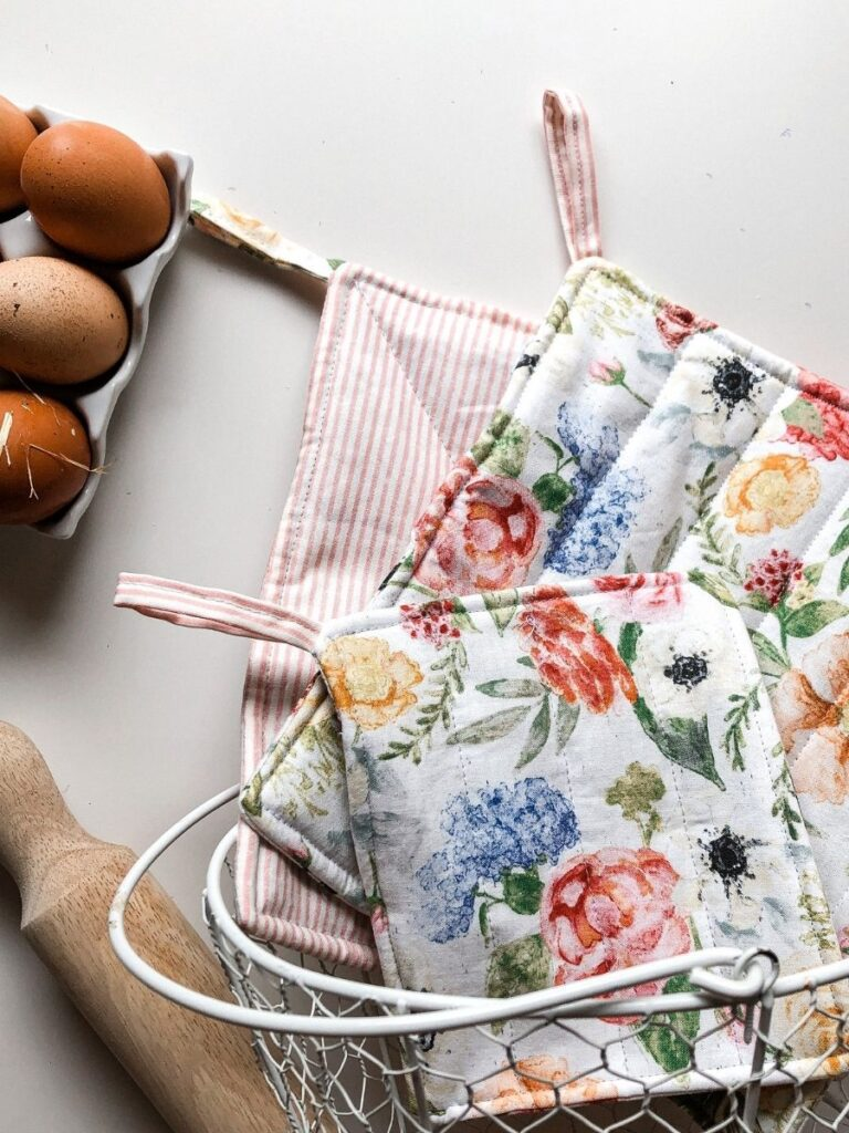floral and striped pot holders in wire basket on kitchen bench. Rolling pin and eggs in the background.