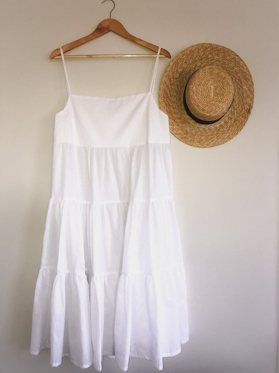how to make a tiered maxi dress is hanging on the wall next to a straw hat.
