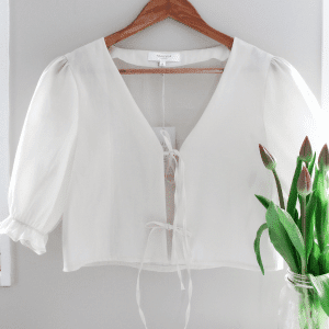Silk Camille Top hanging on wall with tulip flowers in vase.