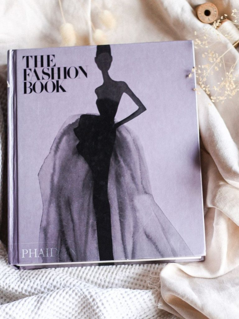 The Fashion Book by Phiadon. Flat lay of book cover sitting on top of beige linen. There are whimsical flowers around the book with wooden spools.