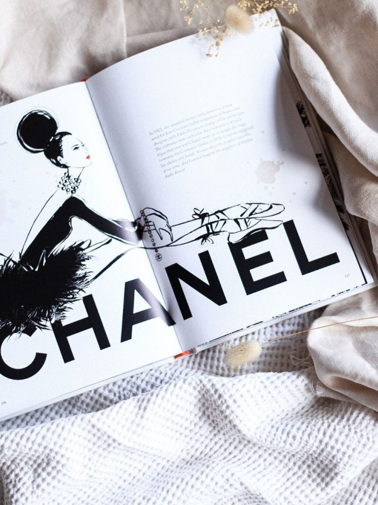 What fashion books you should be reading. Flatlay of book Coco chanel by Megan Hass. There are dainty beach straws and coffee in the background.
