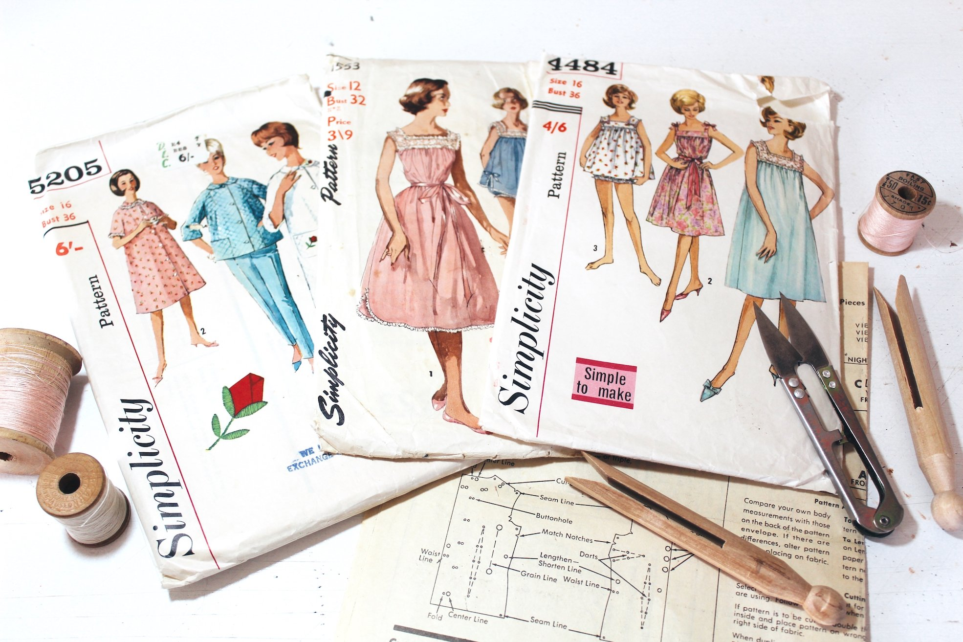 5 sewing tips for beginners sewing patterns laying on table with spools and snips